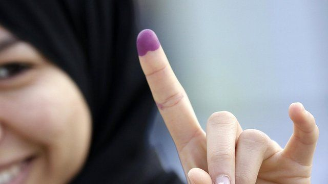 A woman shows her ink-stained finger after casting her vote at a polling station in Tunis