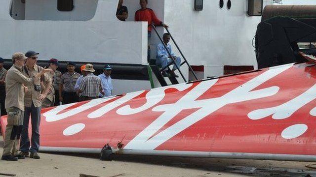 Investigators examine the tail of AirAsia flight QZ8501 in Kumai, 12 January