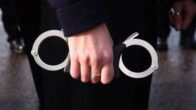 A police recruit at Hendon Police training centre in North London grips a pair of handcuffs