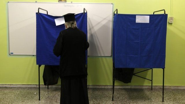 A Greek orthodox priest enters a voting booth