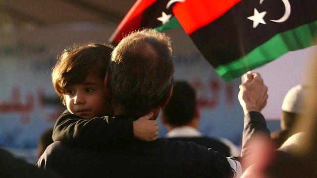 Child and man waving Libya flag