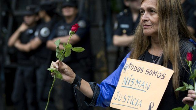 """A woman holding roses wears a sign that reads in Spanish """"We""""re all Nisman. Justice"""" near the funeral home where a private wake is held for prosecutor Alberto Nisman in Buenos Aires"""