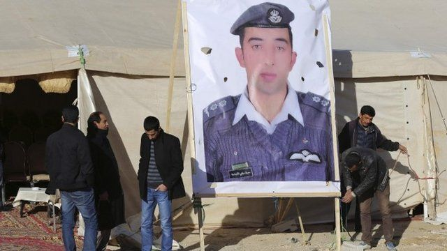 Relatives of Islamic State captive Jordanian pilot Lt Moaz al-Kasasbeh place a poster of him in front of their new gathering headquarters in Amman January 30, 2015