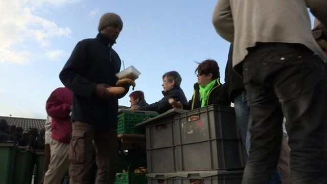 Migrants queue for food