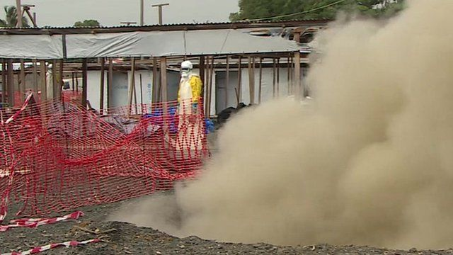 Person in protective gear watches smoke from a fire as an MSF Ebola centre in Monrovia is decommissioned
