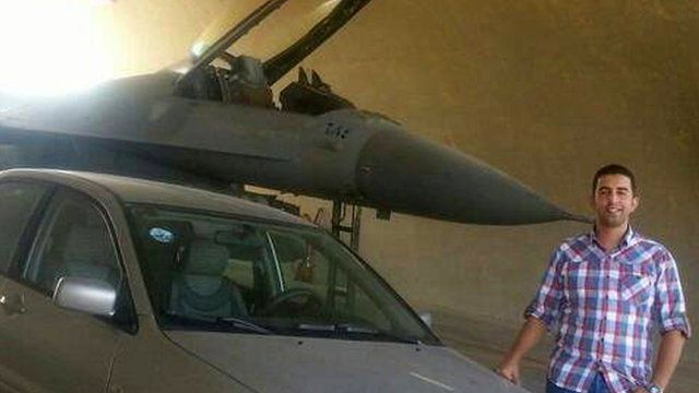 Moaz al-Kasasbeh next to a fighter jet and a car