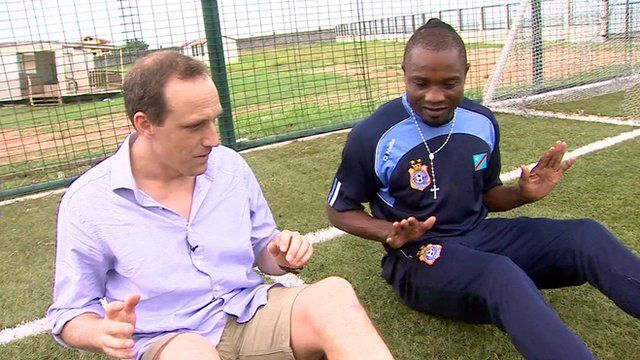 The BBC's Piers Edwards attempts to copy Kidiaba's bouncing bottom
