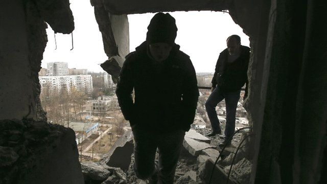 Municipal officials tour a residential block in Donetsk to assess the damage caused by what locals said was a shelling