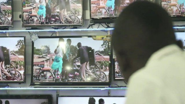 A man watches several TV screens