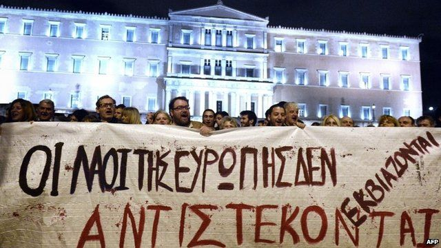 People hold a banner reading ''the people of Europe won't be blackmailed, they will resist'' in front of the Greek parliament in Athens