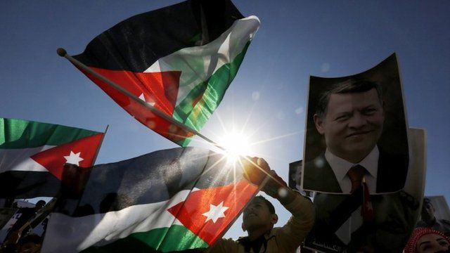 Jordanian protesters hold up pictures of Jordanian King Abdullah in Amman on Thursday 5 February 2015