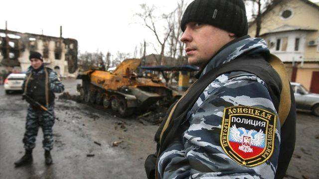Members of the police of the separatist self-proclaimed Donetsk People's Republic gather near a burnt-out armoured vehicle in Vuhlehirsk, Donetsk region