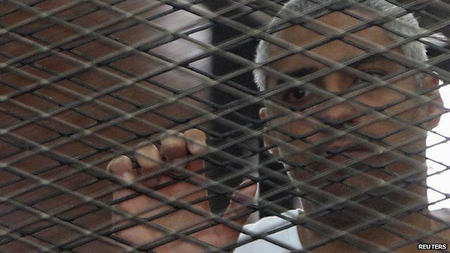 File picture of imprisoned al-Jazeera journalist Mohamed Fahmy behind bars in a Cairo courtroom during his initial trial