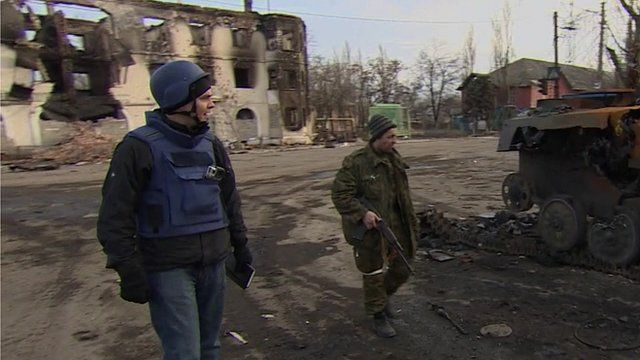 BBC reporter James Reynolds in the rebel-held town of Vuhlehirsk with an armed separatist fighter next to an abandoned APC
