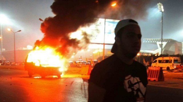 A football fan near a burning police car