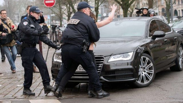 Police detain a topless Femen activist who jumped on the car carrying former IMF chief Dominique Strauss-Kahn