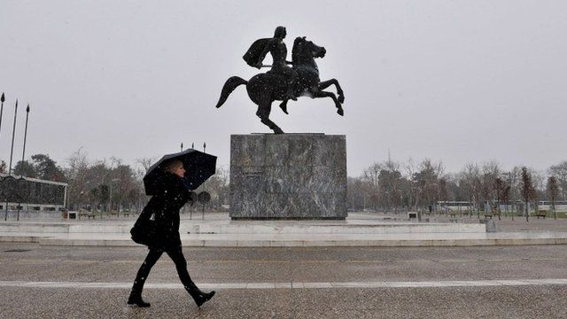 A woman walks past the statue of Alexander the Great under the shelter of her umbrella as snow falls in Thessaloniki on February 9, 2015