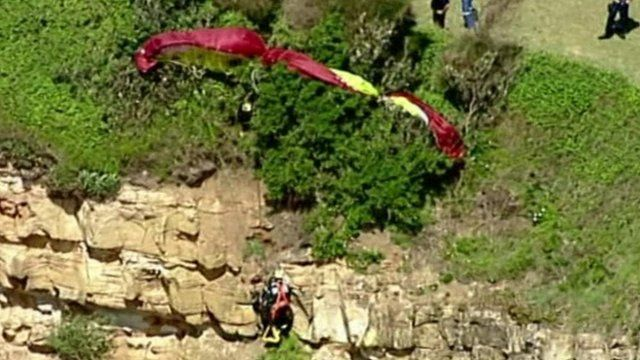 The paraglider can be seen dangling from the rock face