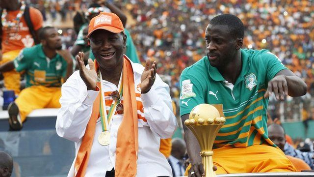 Ivorian President Alassane Ouattara and Ivory Coast captain Yaya Toure wave at the crowd