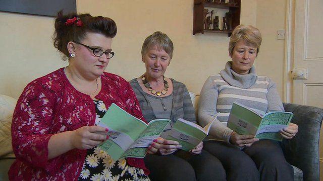 Three women holding their book