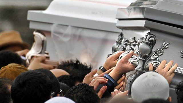 Caskets are carried to waiting vehicles after the funerals