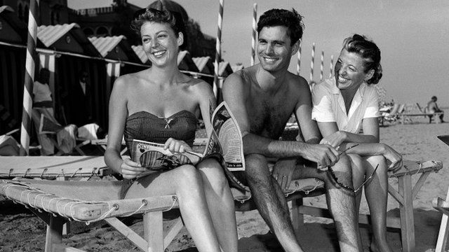 Actor Louis Jourdan sits with actress Anne Vernon, left, and his wife Berthe Fredrique on the beach at Lido isle in Venice, Italy.