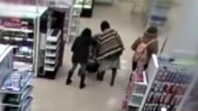 Woman grabs at a baby in a push chair, in Boots in central London