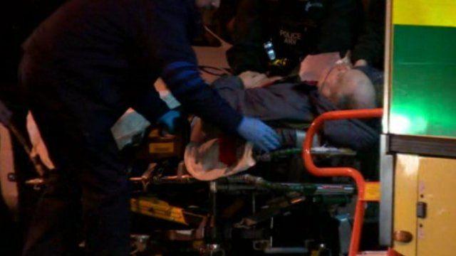 Prisoner being wheeled into ambulance