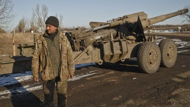 An Ukrainian serviceman stands next to an artillery piece outside Artemivsk, Ukraine, after pulling out of Debaltseve
