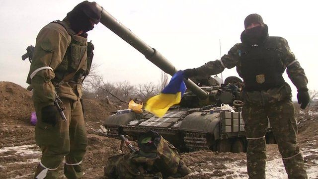 Ukraine rebels in front of a tank