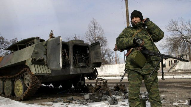 Pro-Russian separatist stands next to damaged military vehicle in the eastern Ukrainian city of Uglegorsk