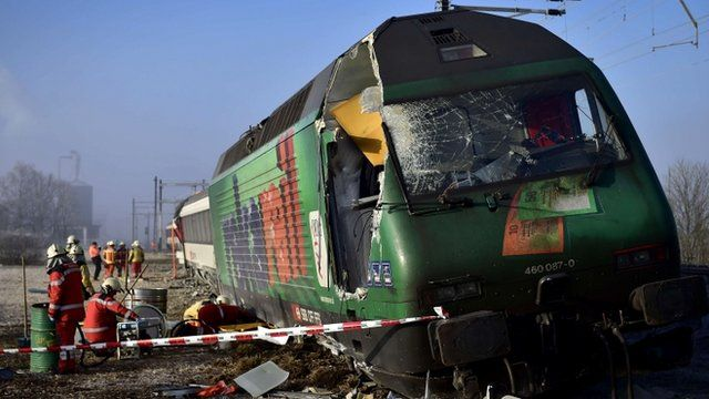 Rescue workers inspect the site of a train crash at the train station of Rafz, northern Switzerland