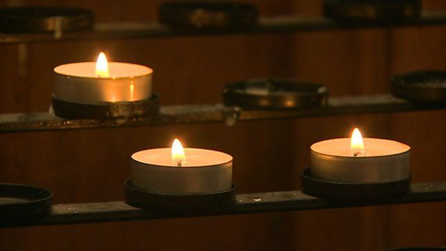 Candles lit at the service for Cameron Comey