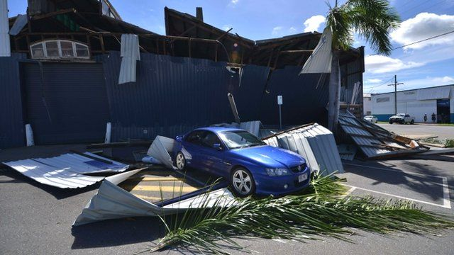 A car sits amongst debris of a cyclone damaged business in northern Queensland