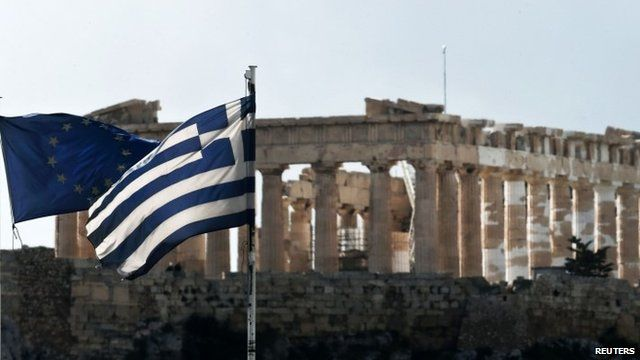 A European Union and Greek national flag are seen in front of the Parthenon temple in Athens