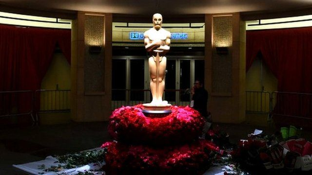 An Oscar statue is surrounded with roses during preparations ahead of the 87th Academy Awards