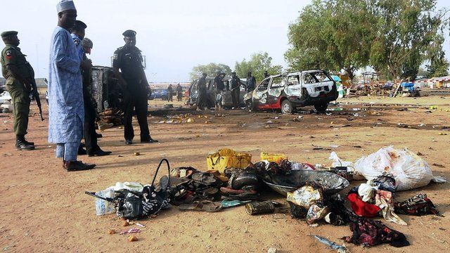 Police officers stand next to personal effects abandoned at the scene of a twin suicide blast