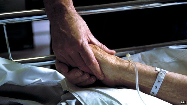 Close up of hand holding the hand of an elderly patient with an IV drip