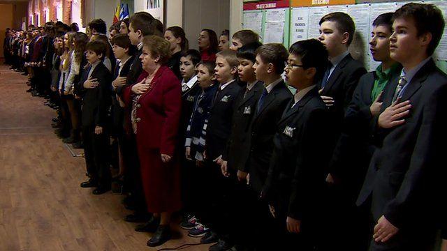 Mariupol high school students sing the national anthem of Ukraine