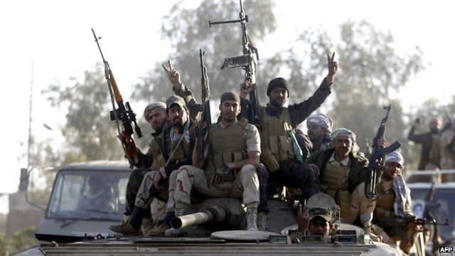 Iraqi security forces and Shiite fighters sit on a tank in the Salahuddin province 2 March, 2015