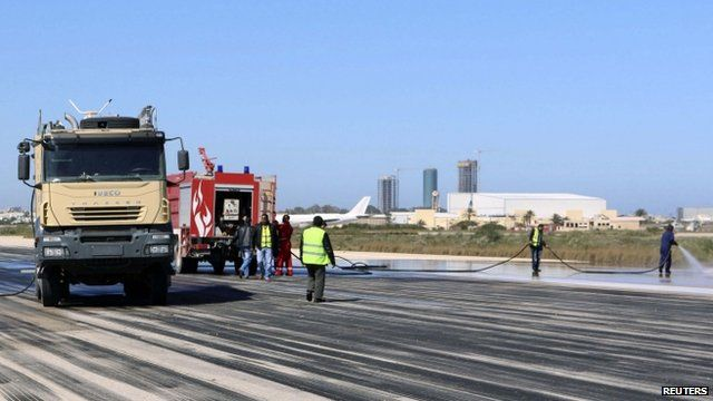 Fire brigade workers clean the runway after an airstrike hit Tripoli's Maitiga airport 3 March, 2015