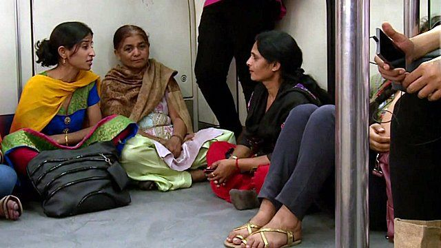 Women sitting on the floor, talking, in the ladies coach