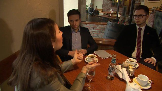 Katya Adler in a coffee house with two Lithuanian students
