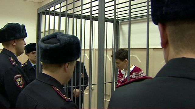 Nadiya Savchenko in a cell surrounded by Russian guards
