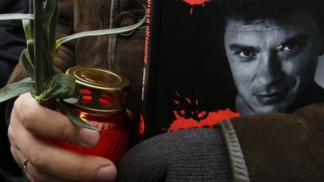 A mourner clutches a book bearing a photo of Boris Nemtsov in Moscow, 3 March