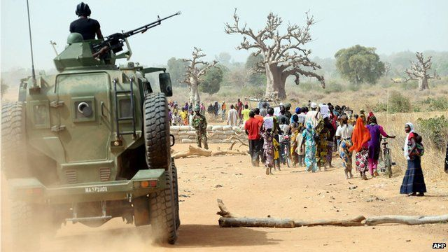 A Nigerian army armoured car gives cover to Chibok women as they walk along a road in north eastern Nigeria, on 5 March, 2015