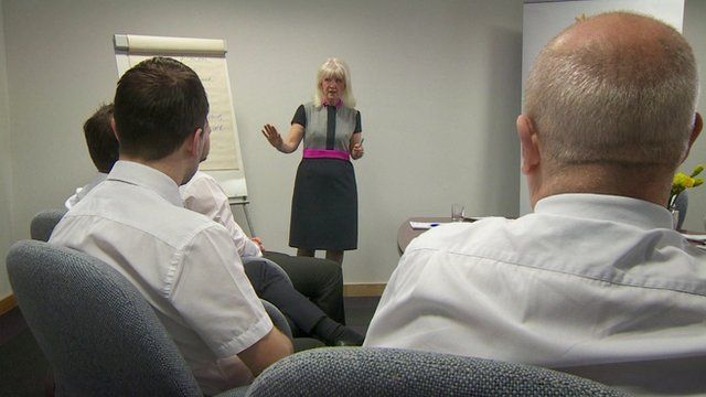 Kathryn Colas, consultant, speaking to group of men in office