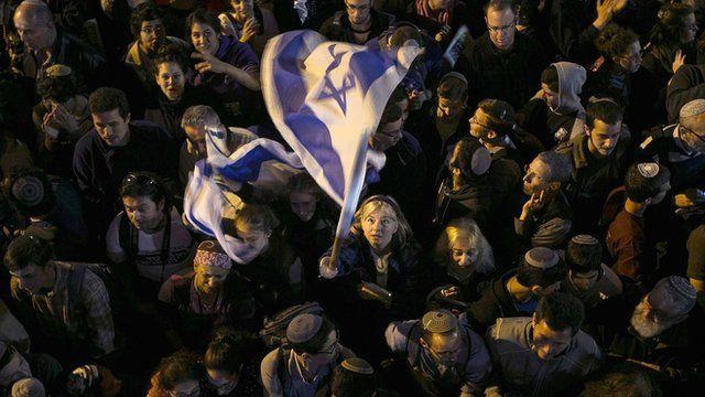 Woman in crowd waving an Israeli flag