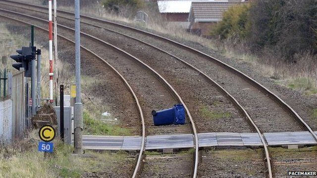 Police are examining a bin which is on the railway line between Lisburn and Portadown