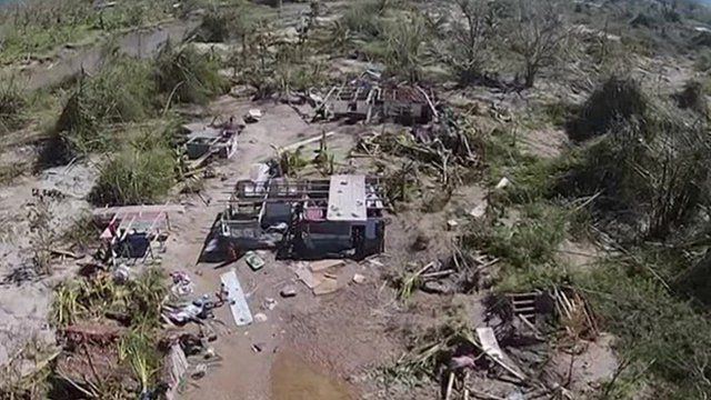 Aerial shot showing ripped up trees and destroyed buildings